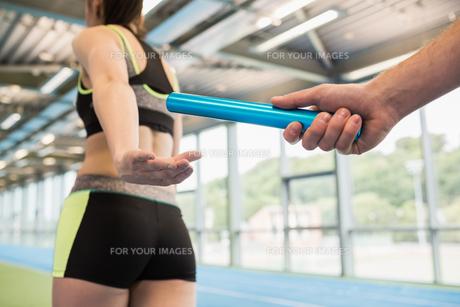 Man passing the baton to partner on trackの写真素材 [FYI00486146]