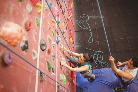 Instructor guiding woman on rock climbing wallの写真素材 [FYI00486156]