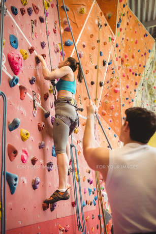 Instructor guiding woman on rock climbing wallの素材 [FYI00486159]