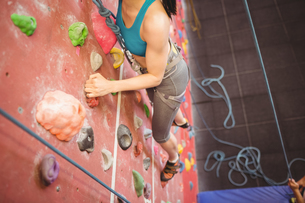 Instructor guiding woman on rock climbing wallの写真素材 [FYI00486160]