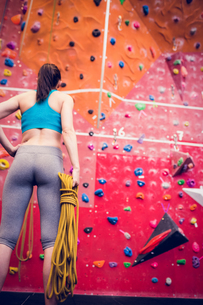 Fit woman looking up at rock climbing wallの写真素材 [FYI00486161]