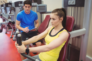 Fit woman using weights machine with trainerの写真素材 [FYI00486165]