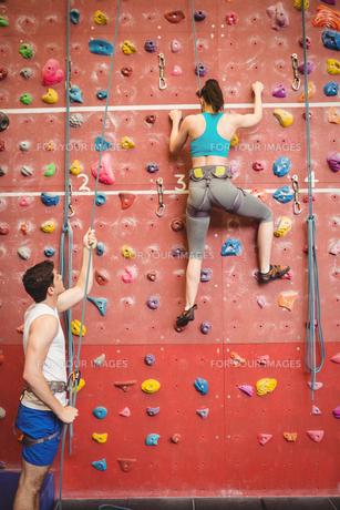 Instructor guiding woman on rock climbing wallの素材 [FYI00486175]