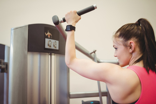 Fit woman using weights machine for armsの写真素材 [FYI00486177]