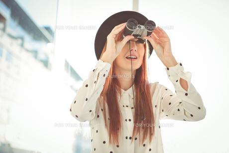 Smiling hipster woman using binocularsの素材 [FYI00486186]