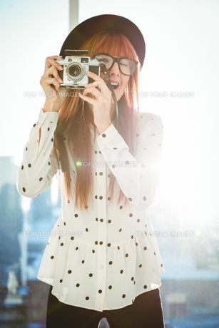 Smiling hipster woman taking picturesの写真素材 [FYI00486190]