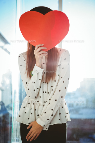 Attractive hipster woman behind a red heartの写真素材 [FYI00486192]