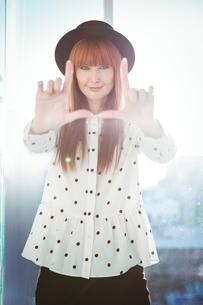 Smiling hipster woman do a framing with her handsの写真素材 [FYI00486193]