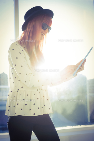 Smiling hipster woman using her tabletの写真素材 [FYI00486194]