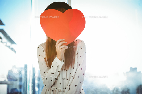 Attractive hipster woman behind a red heartの写真素材 [FYI00486196]