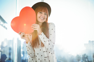 Attractive hipster woman behind a red heartの写真素材 [FYI00486197]