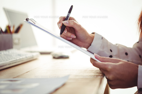 Cropped image of woman writing on clipboardの素材 [FYI00486212]