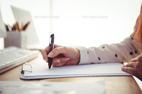 Cropped image of woman writing on notepadの素材 [FYI00486215]