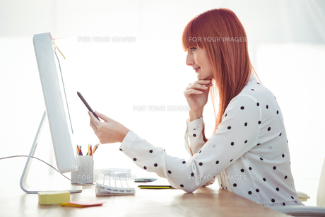 Smiling hipster woman pointing screen with penの素材 [FYI00486217]