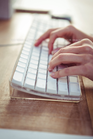Cropped image of woman typing on keyboardの素材 [FYI00486218]