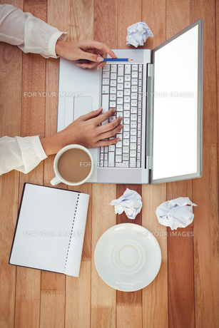 Cropped image of woman with pen using laptopの素材 [FYI00486228]