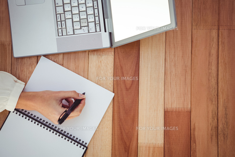 Cropped image of woman writing on notepadの素材 [FYI00486229]
