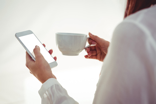 Woman with red hair using smartphone and holding coffee cupの写真素材 [FYI00486241]