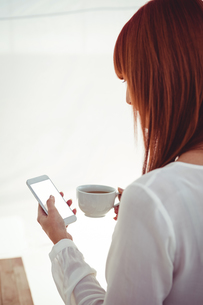 Woman with red hair using smartphone and holding coffee cupの写真素材 [FYI00486242]