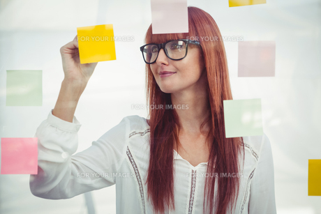 Attractive hipster woman writing on sticky notesの素材 [FYI00486246]