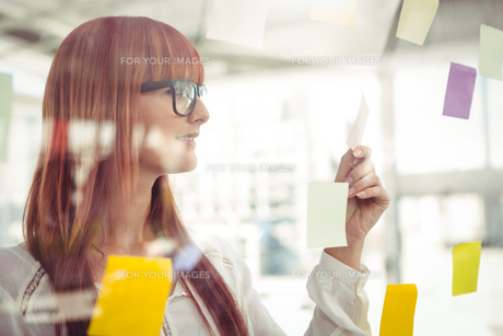 Attractive hipster woman looking at sticky notesの素材 [FYI00486248]