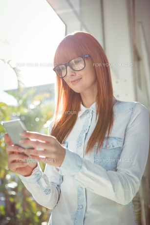 Smiling woman using smartphoneの写真素材 [FYI00486255]