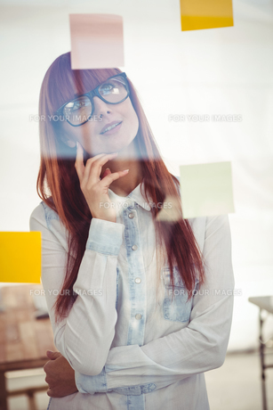 Attractive hipster woman looking at sticky notesの素材 [FYI00486256]