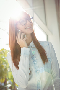 Smiling woman using her smart phoneの素材 [FYI00486258]