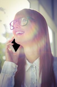Smiling woman using her smart phoneの写真素材 [FYI00486259]