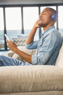 Happy handsome man listening music with headphonesの素材 [FYI00486271]