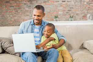 Father and son using laptop on the couchの写真素材 [FYI00486273]
