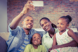 Happy family taking a selfie on the couchの写真素材 [FYI00486274]