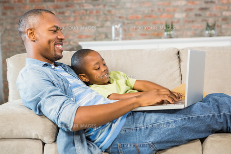 Father and son using laptop on the couchの写真素材 [FYI00486277]