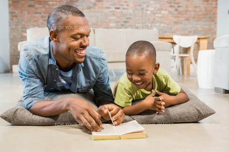 Father and son reading on the floorの写真素材 [FYI00486278]
