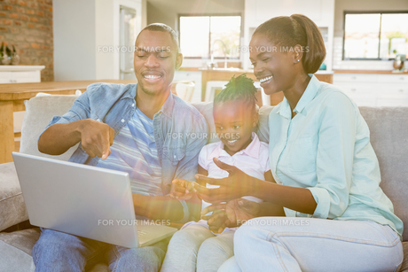 Happy family using laptop on the couchの写真素材 [FYI00486284]