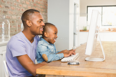 Cute son using laptop at desk with fatherの写真素材 [FYI00486291]
