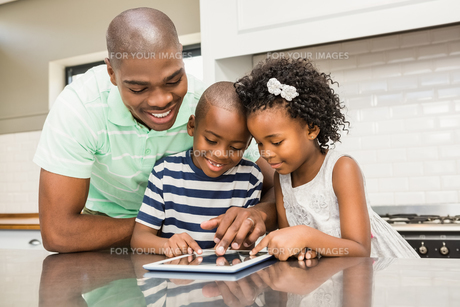 Father using tablet with his children in kitchenの写真素材 [FYI00486294]