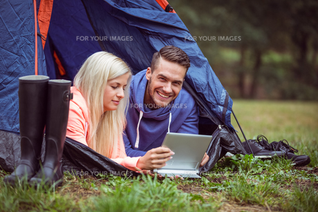 Happy couple lying in their tent using tabletの写真素材 [FYI00486303]