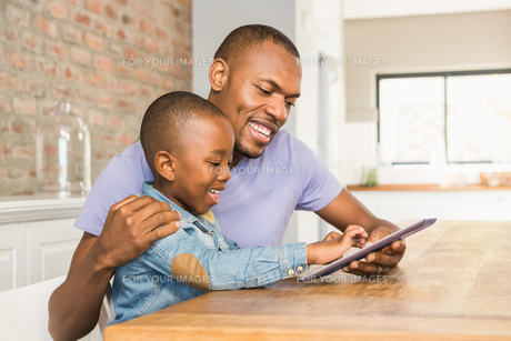 Cute son using tablet at desk with fatherの写真素材 [FYI00486304]