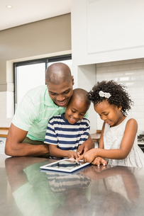 Father using tablet with his children in kitchenの写真素材 [FYI00486309]