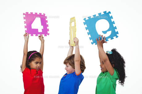 Three kids holding number shanpes above their headsの写真素材 [FYI00486314]