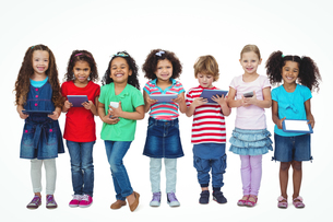 Kids standing together holding tablets and phonesの写真素材 [FYI00486319]