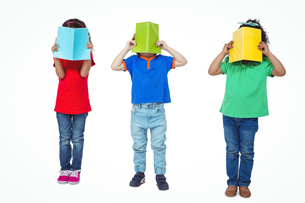 Three kids standing with books in front of their facesの写真素材 [FYI00486323]