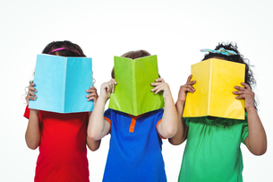 Three kids standing with books in front of their facesの素材 [FYI00486324]