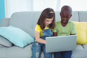 Smiling girl and boy using a laptopの写真素材 [FYI00486325]