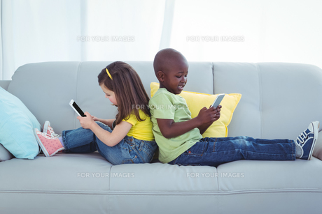 Smiling girl and boy using mobile phonesの写真素材 [FYI00486327]