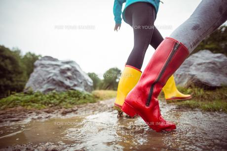 Women splashing in muddy puddlesの素材 [FYI00486332]