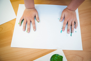 Boy pressing his paint covered handsの写真素材 [FYI00486345]