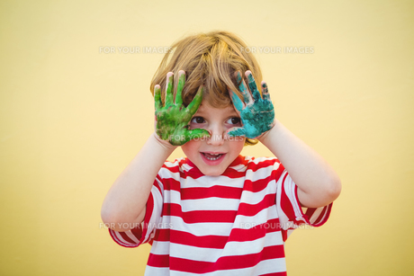 Boy holding his paint covered hands upの素材 [FYI00486347]