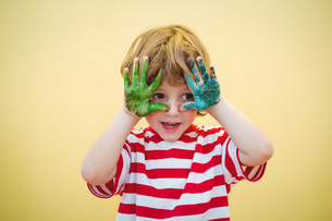 Boy holding his paint covered hands upの写真素材 [FYI00486347]